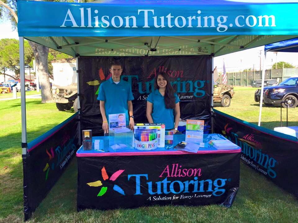 Allison Tutoring custom printed table cover, canopy, back wall, and short walls at an event on a grassy field