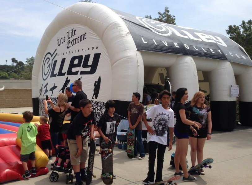 15x30 inflatable tent with printed tent top and wall panels for Olley with event attendees holding their skateboards around the tent