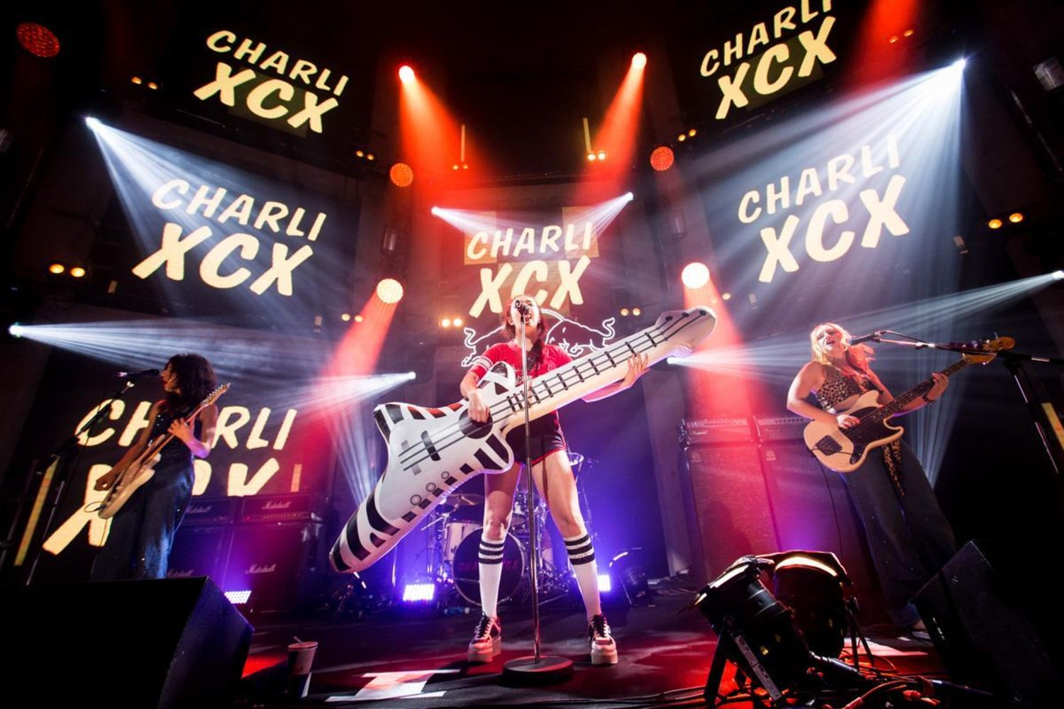Charli xcx concert inflatable guitar prop being used by the lead singer