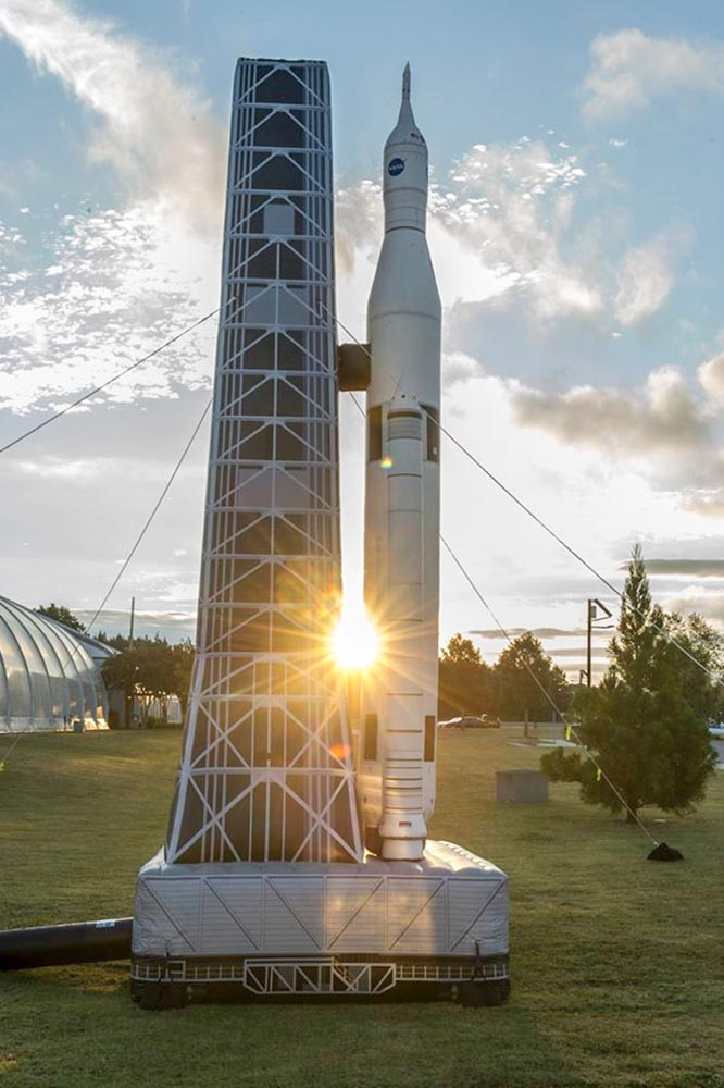 Inflatable NASA space rocket and launch tower with a beam of sunlight emerging from in between the tower and the rocket