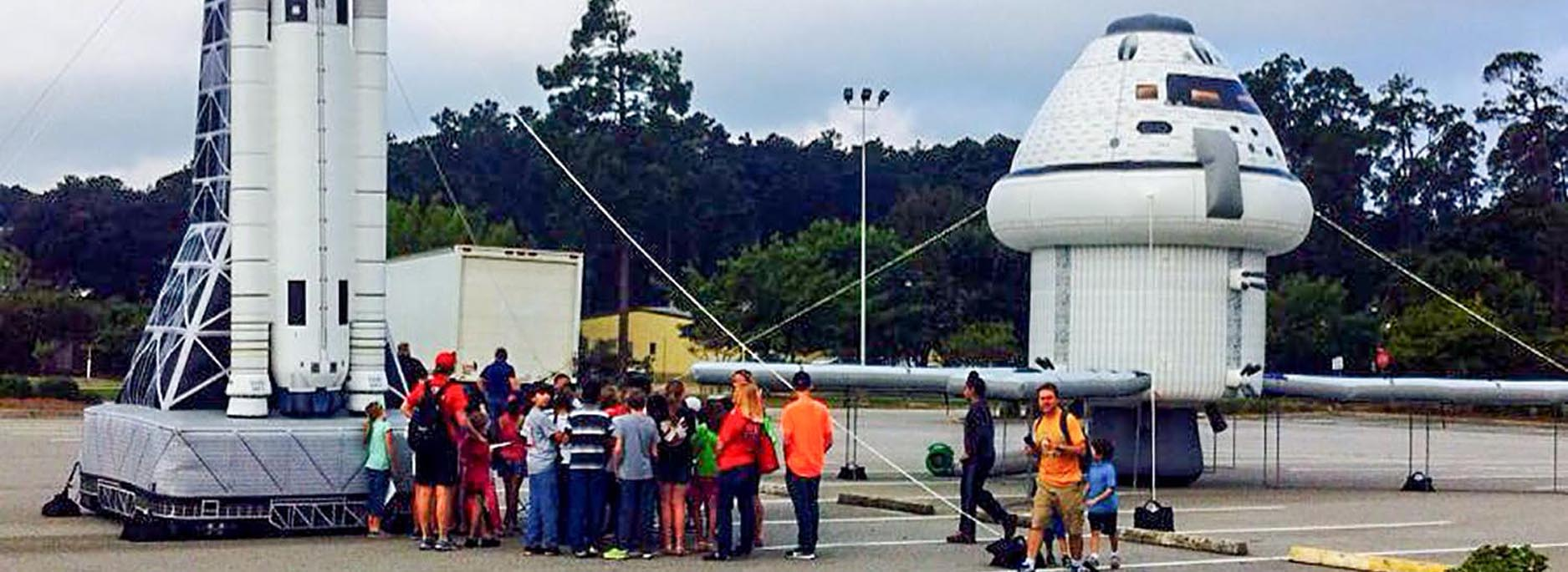 NASA space inflatable rocket and capsule installed at an event with multiple attendees standing next to it