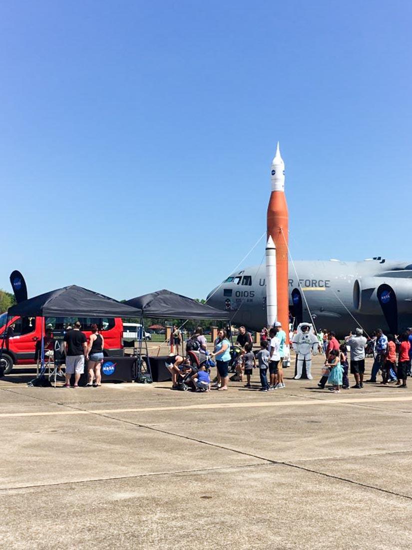inflatable NASA rocket replica next to an air force air-craft