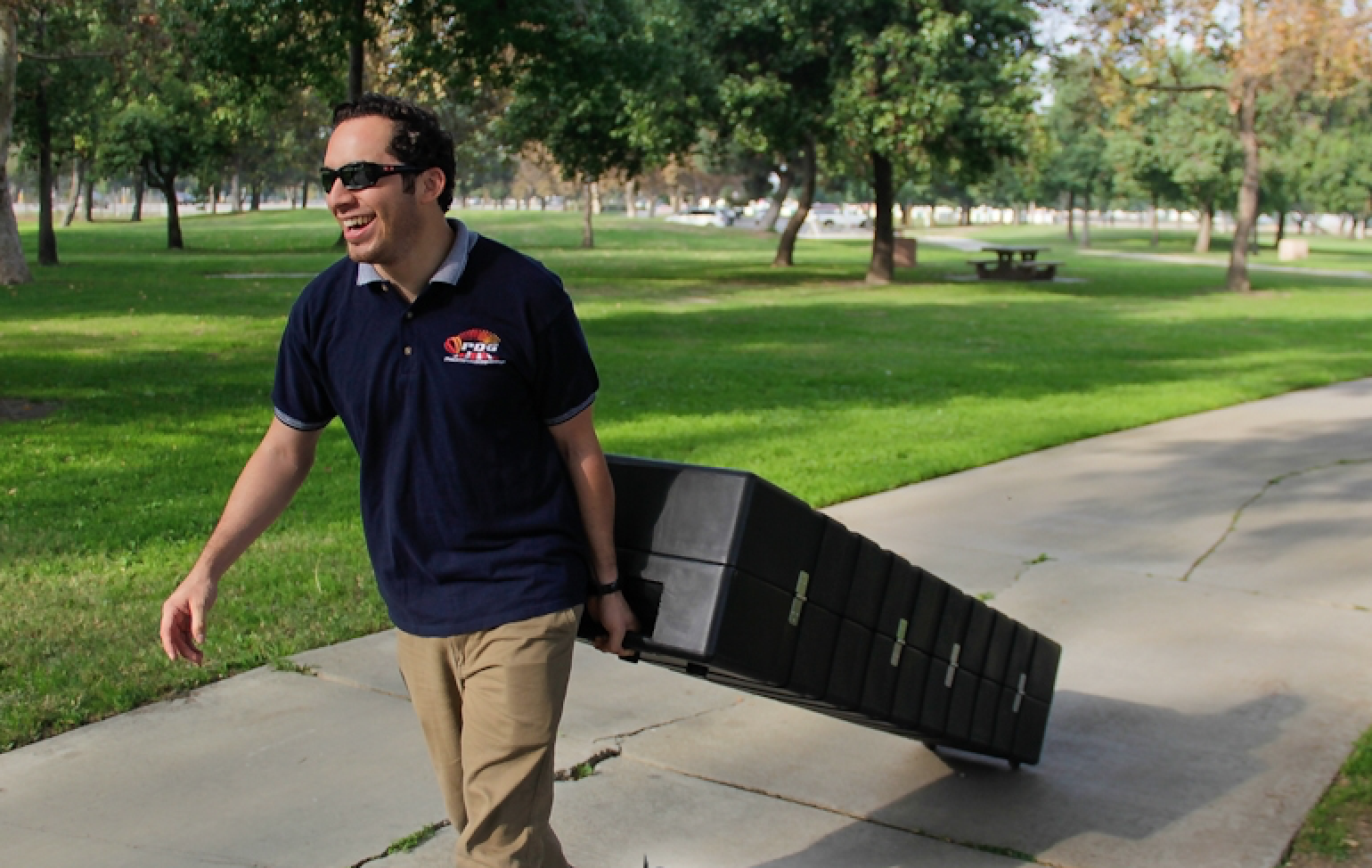 Human pulling a Rhino Roller Hard Case through the park while smiling and wearing sunglasses