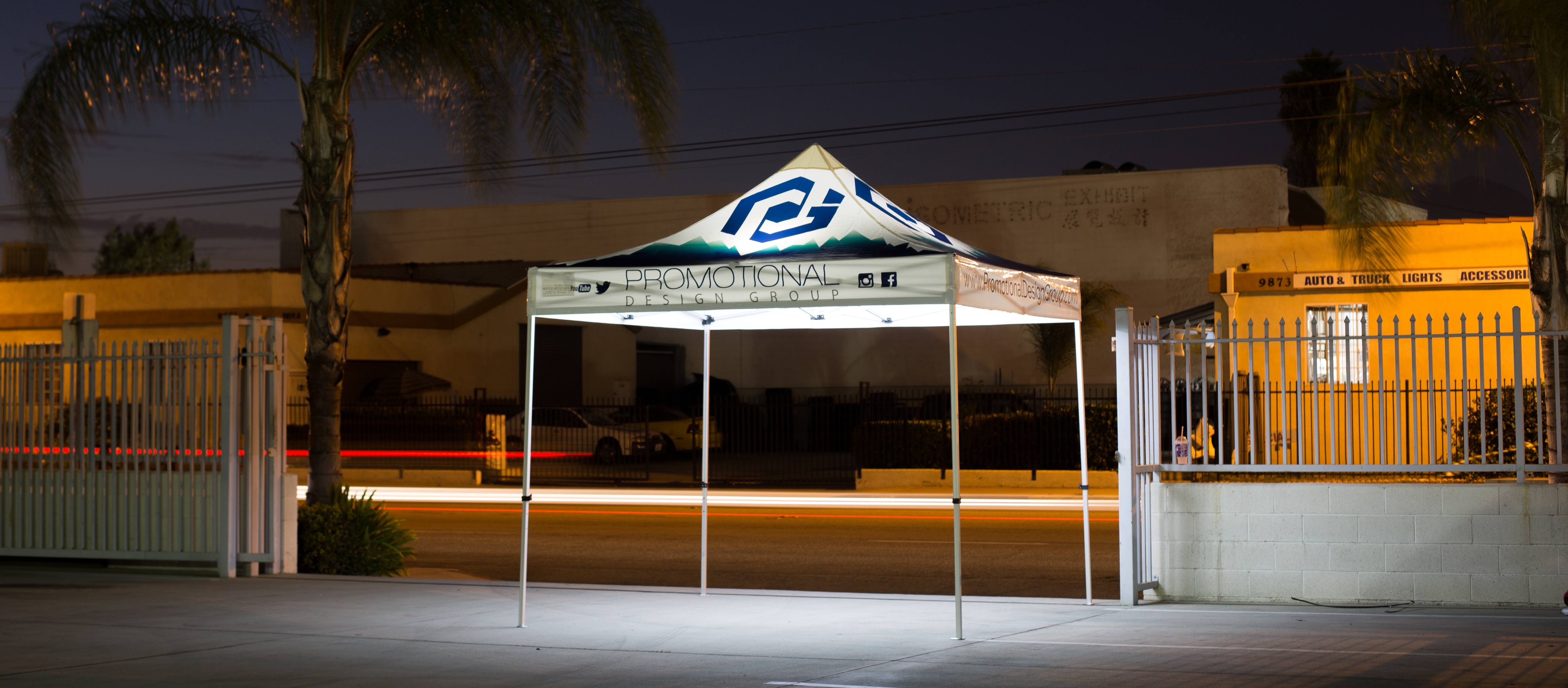Canopy tent lights with a car passing in the background and an illuminated pop up canopy in the forefront