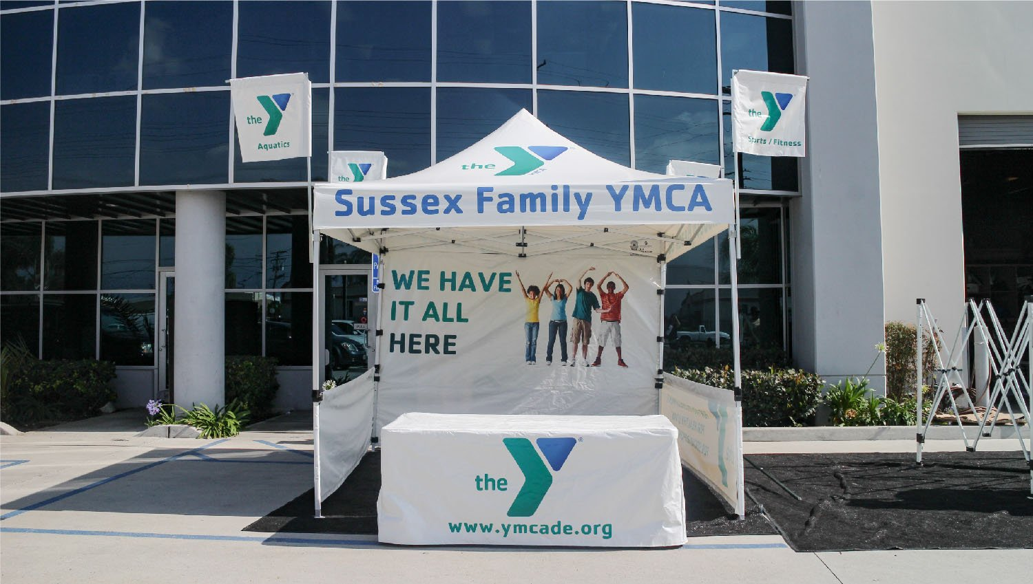 Customized canopy with tent flags on all four corners, printed with the YMCA logo