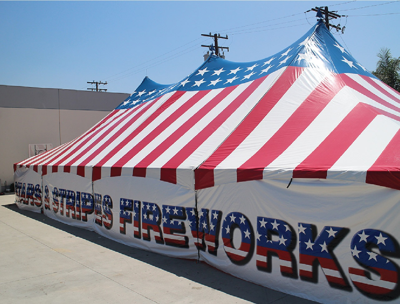 Stars and Stripes USA Patriotic Triple High Peak Frame Tent with stars and straps fireworks printed all across the side of the visible wall