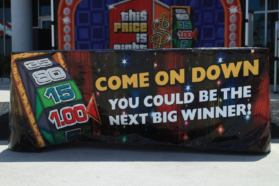 table cover in front of tent with the price is right slogans printed on the front panel of the