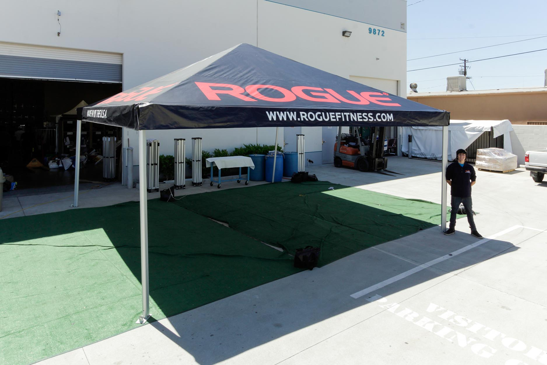Rogue Fitness 20x20 Standard Frame Tent with a printed tent top and a person standing next to it for size comparison
