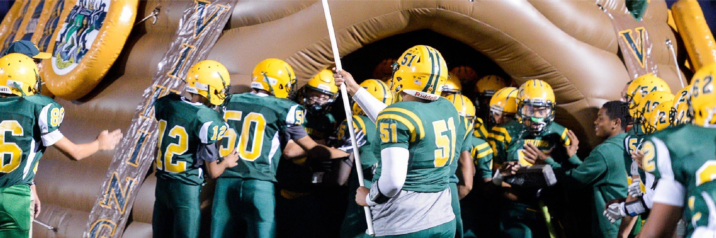Vanden football team huddled around the custom tunnel