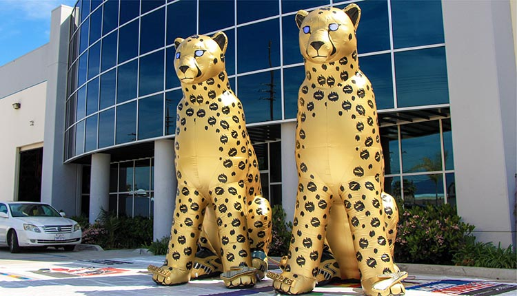 two golden inflatable cheetahs in front of the promotional design group building