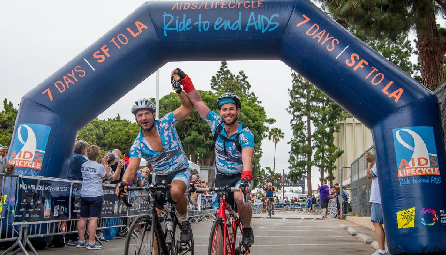AIDS Lifecycle Custom Blue Inflatable Arch with two participants crossing beneath the arch