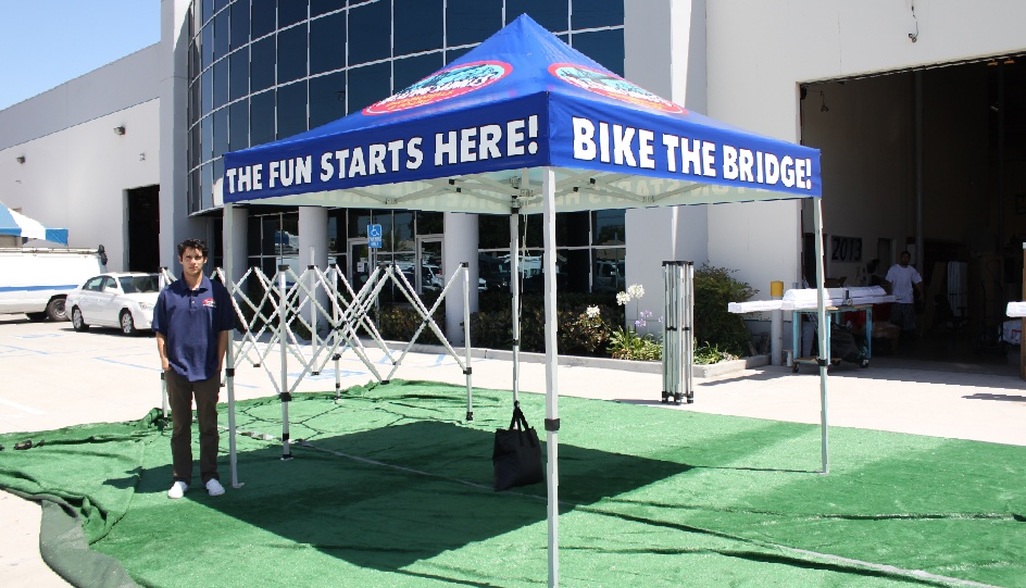 Bronze 10x10 canopy tent package with printed tent top in front of business with pop up tent frames in the background