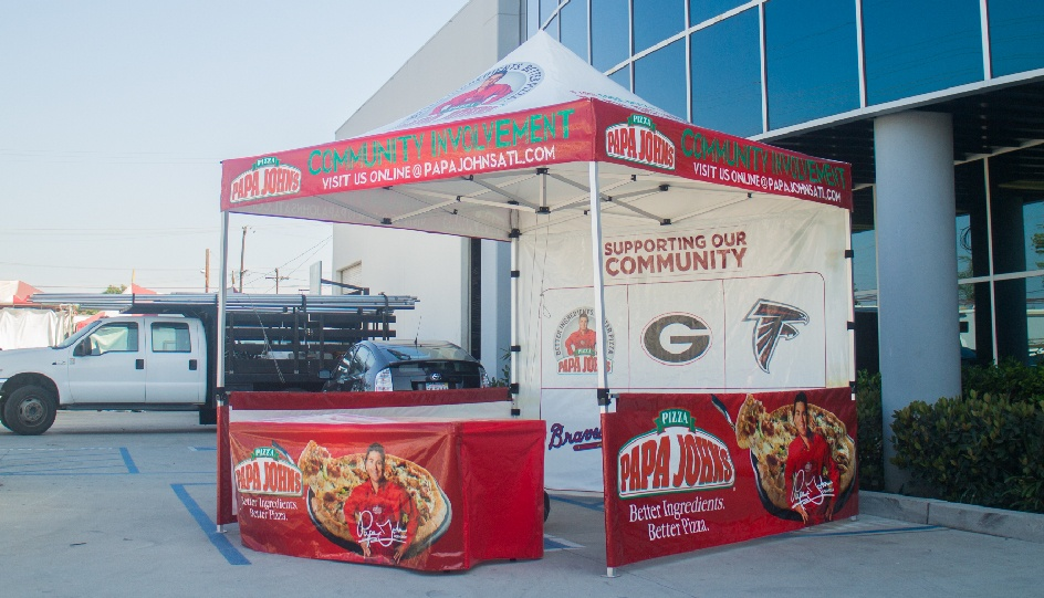 Papa Johns Gold canopy package with printed tent top, printed back wall, printed short walls and rail skirts, and printed table cover in front of business.