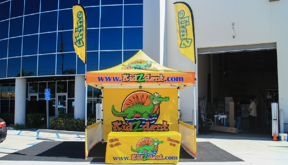 Ad flag canopy package with printed advertising flags, custom tent top, printed back wall, short side walls, and table cover